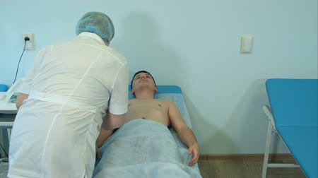 yöntem : Experienced nurse preparing male patient for electrocardiography Stok Video