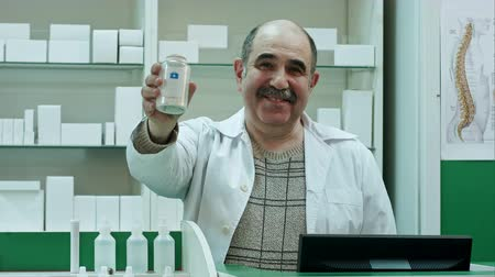 dispensing : Smiling doctor holding up a bottle of tablets or pills with a blank white label for treatment of an illness and look to a camera