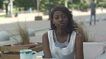 obyčejný : Serious black woman with afro hairstyle, dressed in formal white top, sitting at cafe and waiting for her friend Dostupné videozáznamy