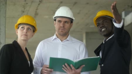 construction work : Portrait of tree builders standing at building site and discussing new project Stock Footage