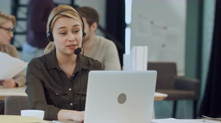 телефон доверия : Smiling female helpline operator with headphones at her desk in the office