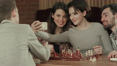 szabály : Group of students playing chess, while taking selfie photo Stock mozgókép