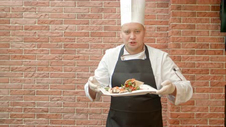 umutlu : Friendly chef in uniform present a plate with seafood salad, talking to a camera