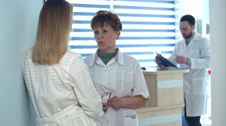 registration : Two nurses talking near reception desk Stock Footage