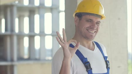 construtor : Cheerful builder showing ok sign