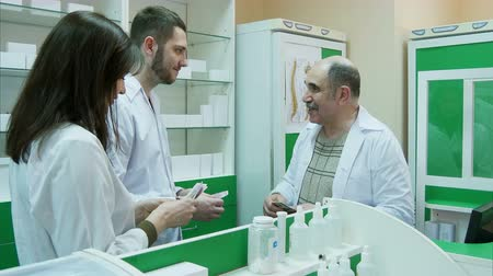med : Senior pharmacist giving salary in dollar to his young colleagues at pharmacy