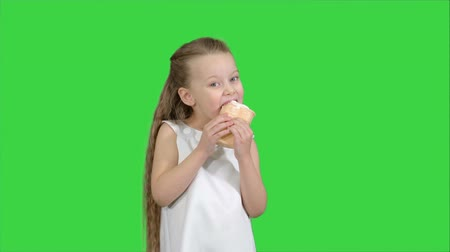 tevreden : Kid girl eating with ice cream on a Green Screen, Chroma Key