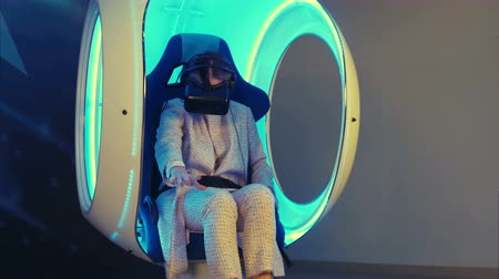 будущее : Emotional woman experiencing virtual reality in a moving interactive chair