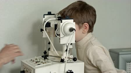 oogmeting : Old male doctor examines eyes of boy through slit lamp