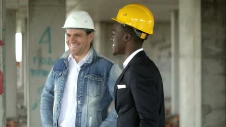 construtor : Cheerful professional construction manager and afro businessman talking and smiling at construction site