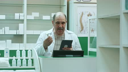 representante : Senior pharmacist having video chat with client using tablet pc in drug store