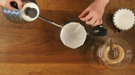 grãos de café : Barista pouring water on coffee ground with filter