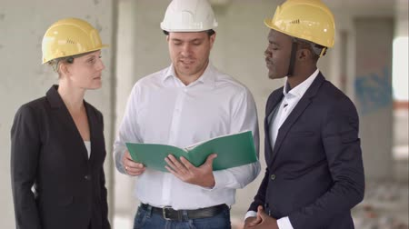 workgroup : Group of smiling builders in hardhats with clipboard and blueprint outdoors Stock Footage