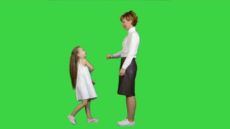 vysoká klíč : Beautiful mother and daughter giving high five and smiling each other on a Green Screen, Chroma Key