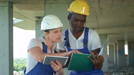 hardhat : Construction team consult and consider plans for the construction