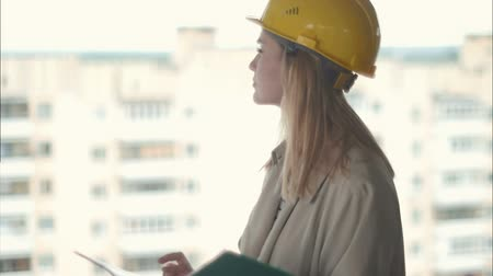 işbirliği yapmak : Female architect looking carefully at plan on construction site Stok Video