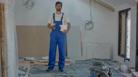 construtor : Smiling young worker standing at building house
