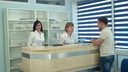 registrace : Medical staff working at busy medical reception desk