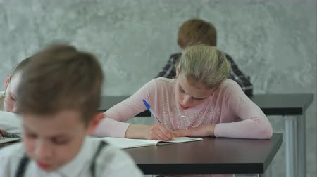 each other : Group of students with notebooks writing test at school
