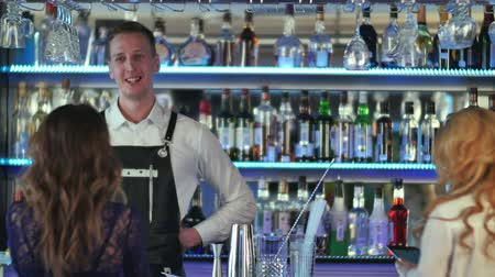 nóbl : Handsome bartender serving cocktail to beautiful woman in a classy bar