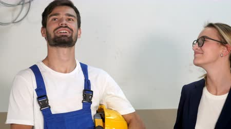 latinamerican : Smiling builders and architects in hardhats at apartment house