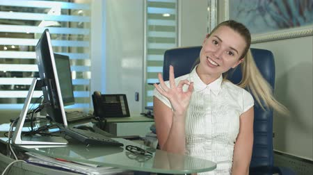 okey : Happy smiling beautiful young businesswoman showing okay gesture sitting in office