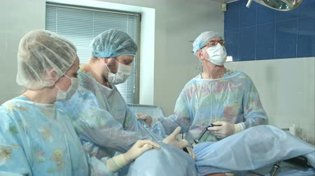 scalpel : Team of doctors working together during a surgery in an operating room at a hospital