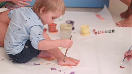 harmanlanmış : Cute little baby boy painting his feet on a large blank white paper Stok Video