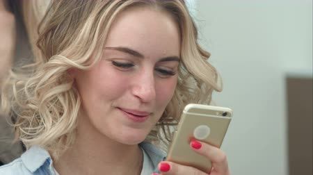 sending : Woman having hair styling in salon while browsing the internet on her mobile phone, smiling
