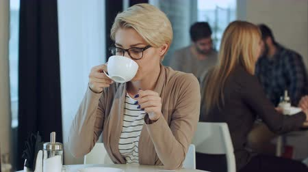 contemplative : Young beautiful woman drinking coffee at cafe bar Stock Footage