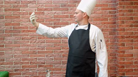pic : Cook chef making selfie via smartphone in the kitchen