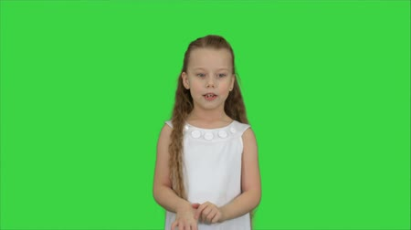looks at the camera : Positive teen girl talking to a camera with a smile on a Green Screen, Chroma Key Stock Footage