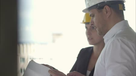 immobilien : Pensive businessman and businesswoman looking at project plan together while working at constructions site