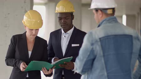 workgroup : Businessman working with Architect Engineer in building Construction Site with blueprint checking plan Stock Footage