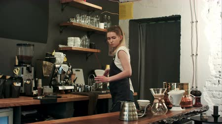 grãos de café : Barista making hand brewed coffee, adding grinded coffee and pouring hot water