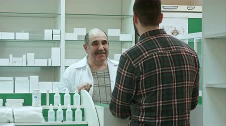 gyógyszerész : Positive senior druggist giving client medicine at the pharmacy Stock mozgókép