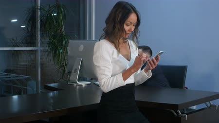 interessado : Asian businesswoman using smartphone in office
