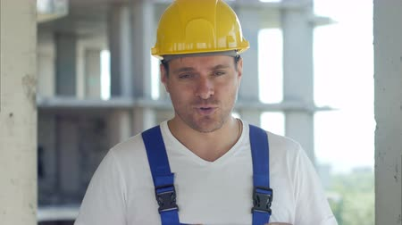 construtor : Construction worker talks to camera in front of building site