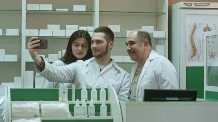 gyógyszerész : Cheerful team of pharmacist and interns take selfie via smartphone at workplace Stock mozgókép