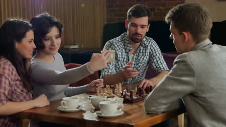 turbina eólica : Young couple playing chess indoor with friends and taking selfie Stock Footage