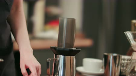 grãos de café : Barista adding grinded coffee and pouring hot water