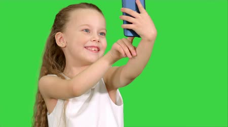 make photo : Little cute girl smile and taking selfie on a Green Screen, Chroma Key