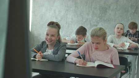 одноклассник : Kids listen to a teacher, answer questions and work on class project Стоковые видеозаписи