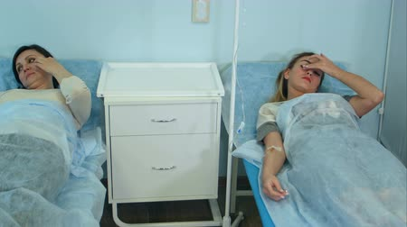 intravenous drip : Two female patients on drips lying on beds in hospital ward being checked by male doctor Stock Footage