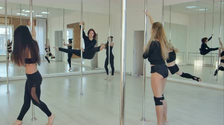 pilon : Group of hispanic women stretching and warming up for their pole dancing class