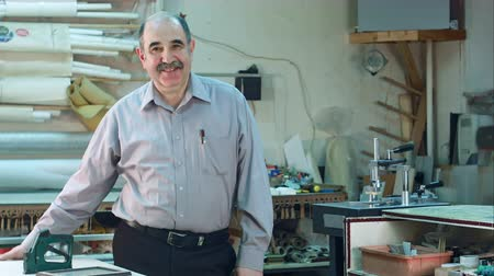 part of the frame : Portrait of a senior male business owner behind the counter of his workshop, standing and smiling to a camera