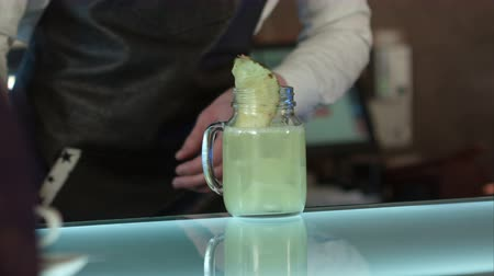 ginástico : The barman at the bar makes cocktail with ice, decorating with a piece of pineapple Stock Footage