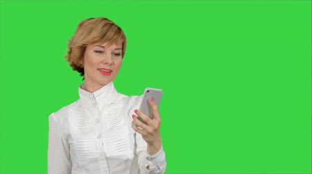 tela : Businesswoman taking funny selfie with phone on a Green Screen, Chroma Key. Stock Footage