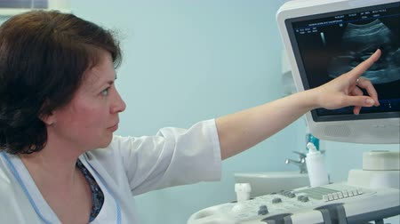 sonography : Smiling female doctor explaining ultrasound results looking at the screen