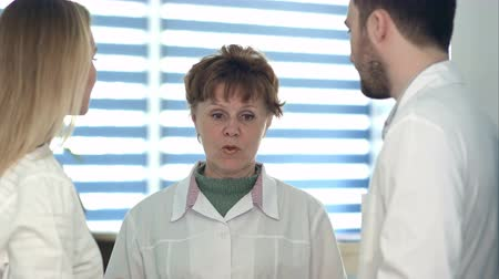 пальто : Female and male doctors talking to an older nurse